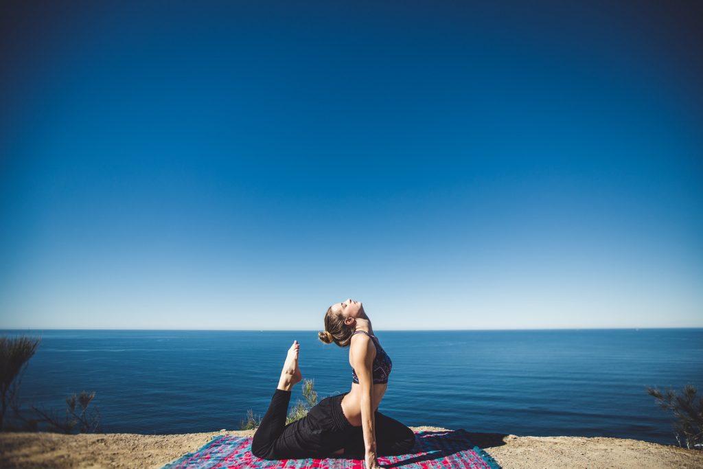 Femme en train de réaliser une pose de yoga au bord de la mer.