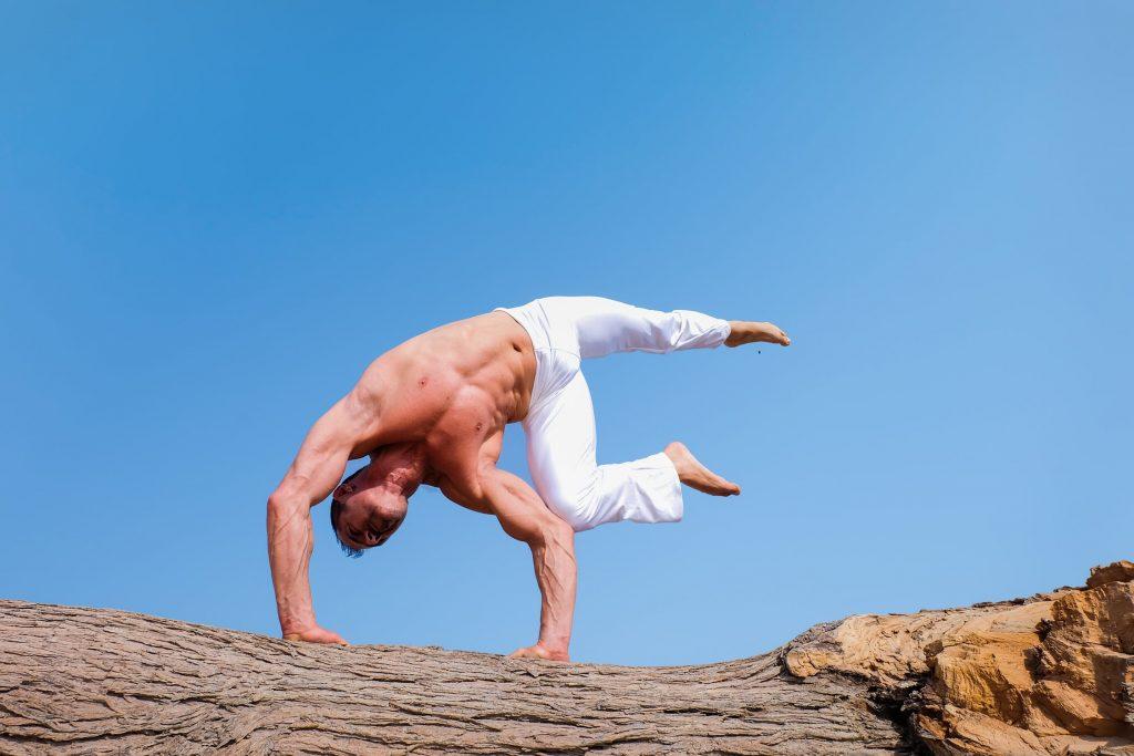 Homme pratiquant du yoga sur un tronc d'arbre