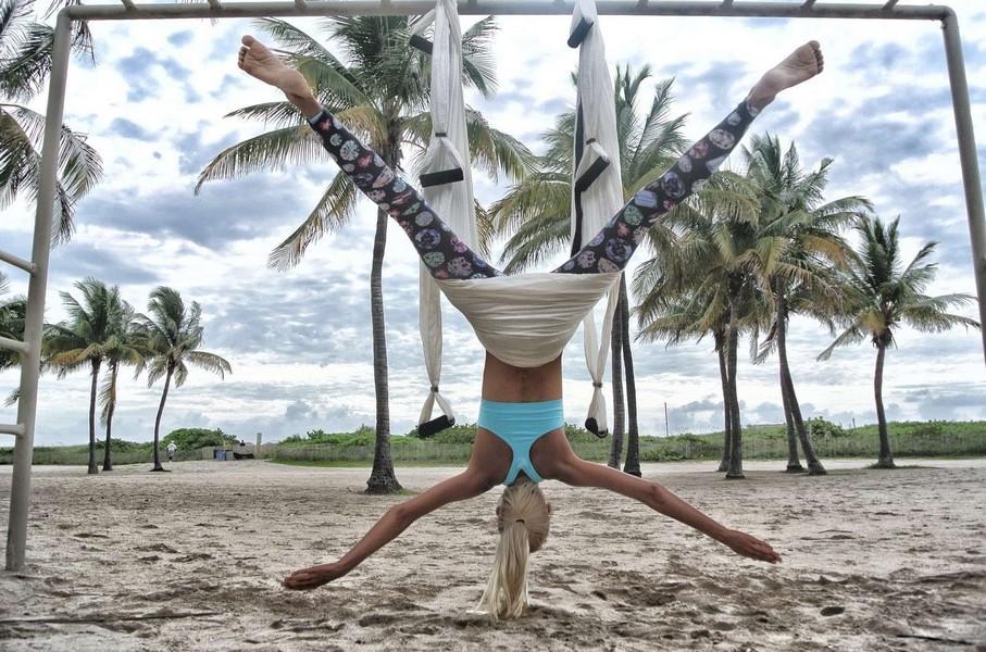 Femme adulte sur la plage faisant du fly yoga ou anti gravity