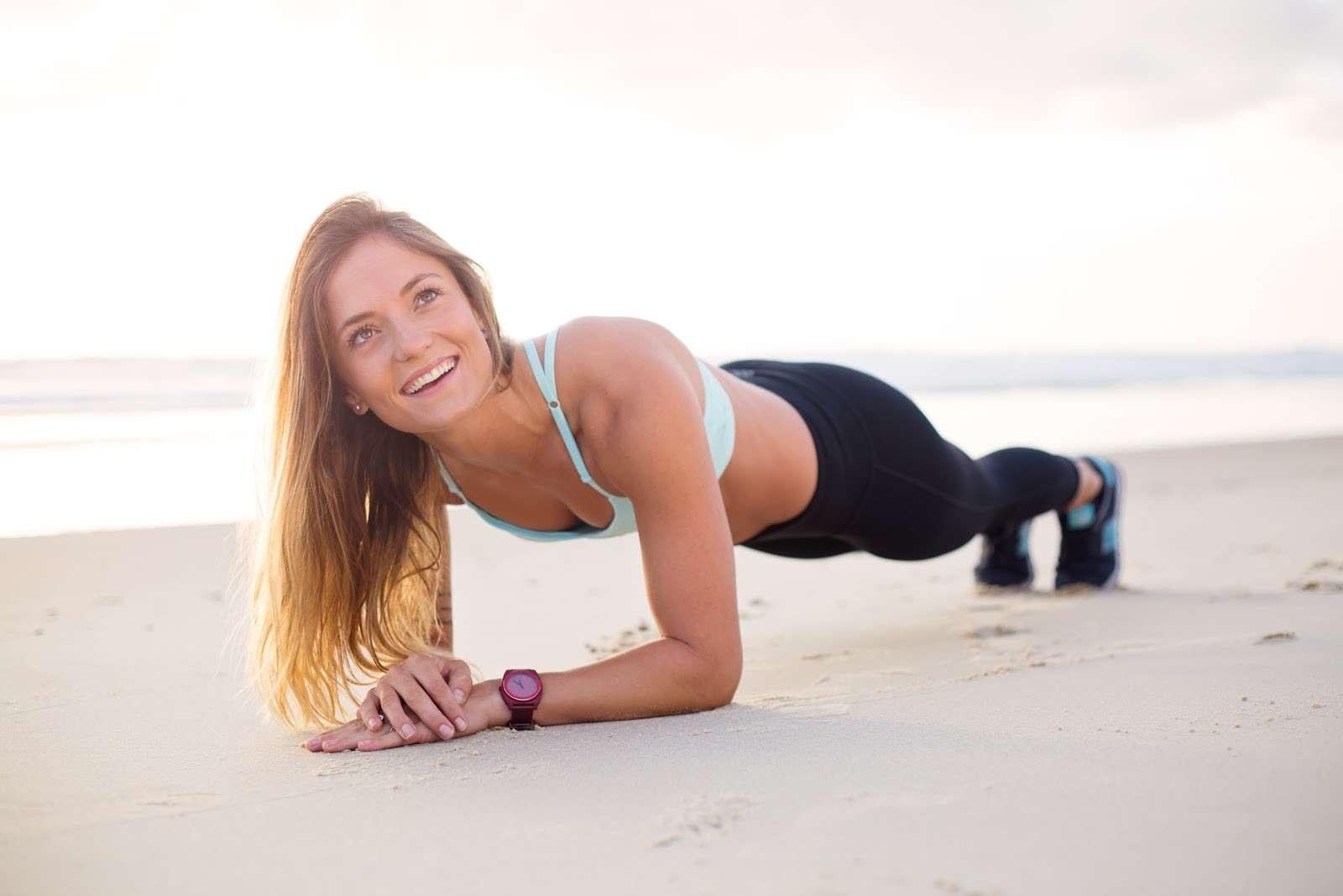 Femme sur le bord de la plage en train de faire la planche pour son cours de Extrême HIIT Yoga