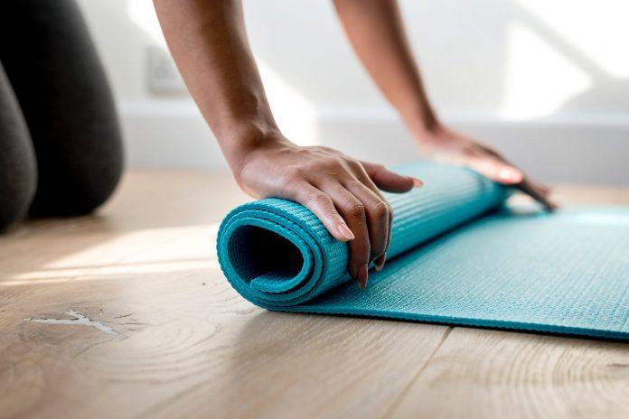 Femme repliant son tapis de yoga