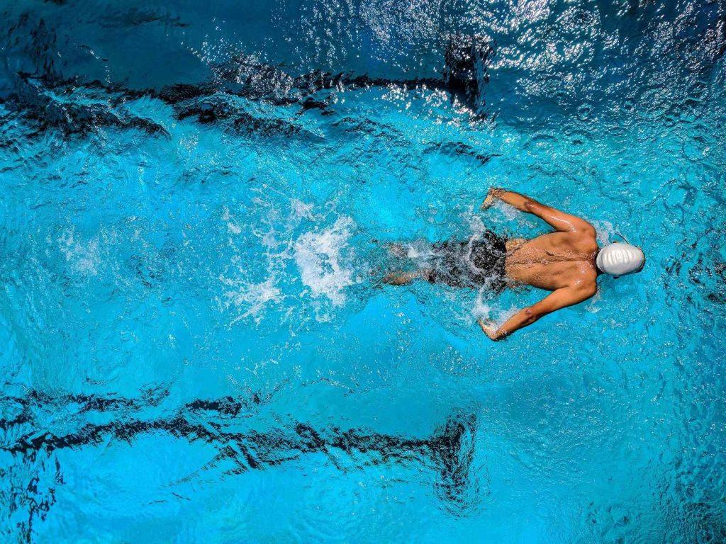 Homme à la piscine pratiquant le swimcross