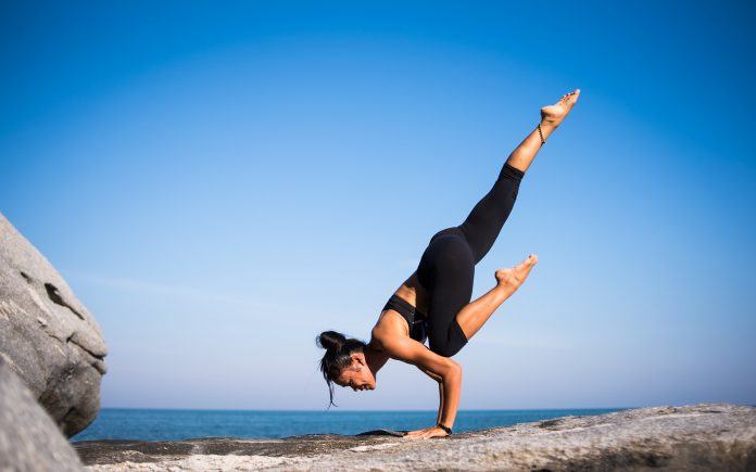 Yogi faisant une posture de yoga devant la mer